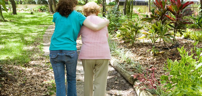 For the Alzheimer's Caregiver | Woman with Alzheimer's walking in a garden with her carer