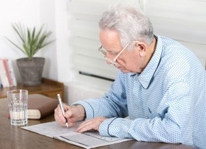 Alzheimer's FAQ |Older man solving a crossword puzzle.