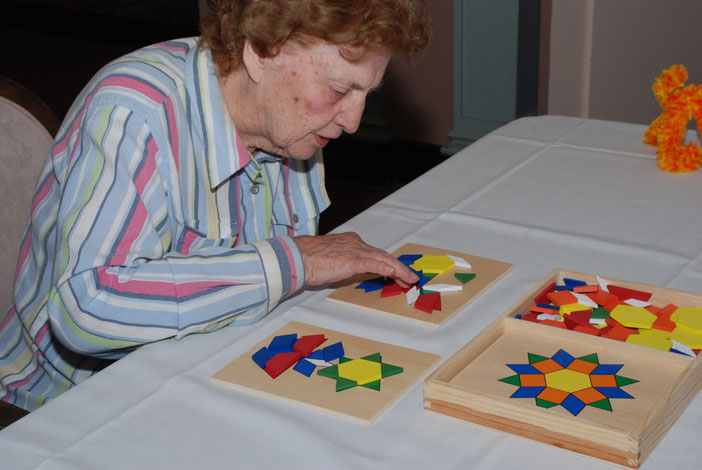 Activities for Alzheimer's disease | An older woman enjoying a puzzle from Best Alzheimer's Products store